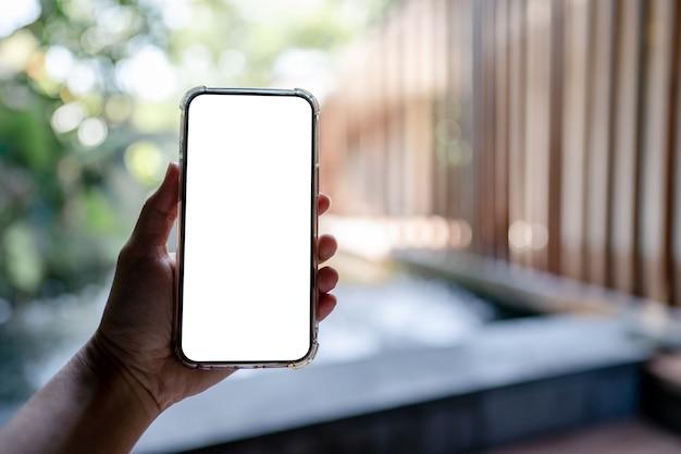 Mãos segurando um telefone celular branco com simulação de tela em branco, spa do hotel.