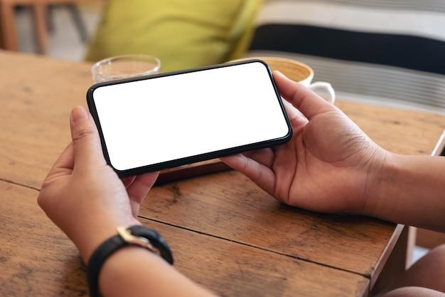 Mãos segurando um telefone celular preto com tela em branco horizontalmente com uma xícara de café na mesa de madeira no café