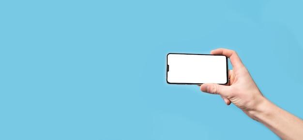 Mãos segurando um telefone celular, smartphone com tela branca sobre um fundo azul. mock up. pode usar mock-up para seu aplicativo ou projeto de design de site da web. espaço para texto. banner.