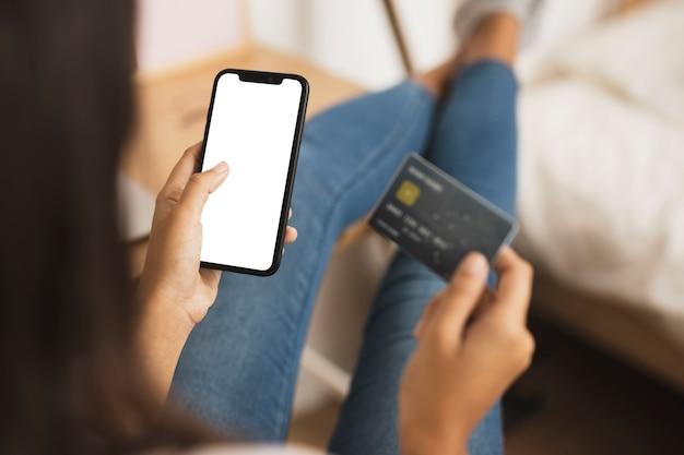 Mãos segurando um telefone e cartão simulado