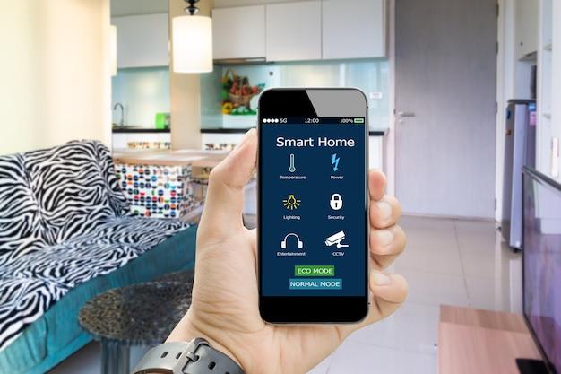 Mãos segurando um telefone inteligente com app para casa inteligente no quarto com cama desfocada