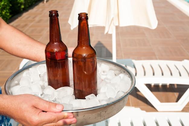 Mãos segurando uma bandeja cheia de cubos de gelo e cerveja