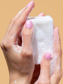 Mãos segurando uma barra de sabão espumoso