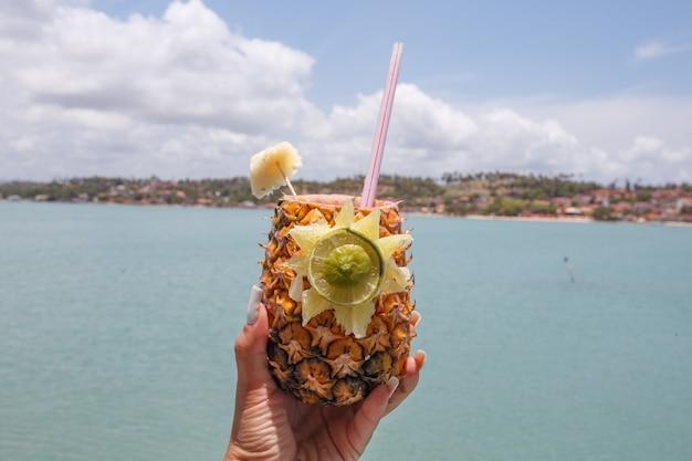 Mãos segurando uma bebida de abacaxi com fundo de praia.