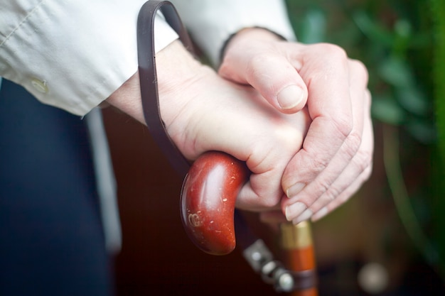 Mãos segurando uma bengala