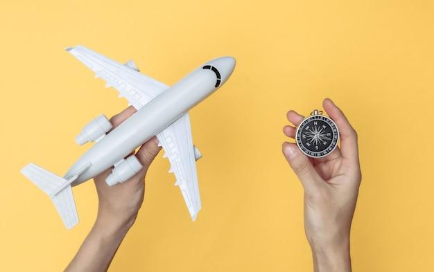 Mãos segurando uma bússola e um avião de brinquedo em fundo amarelo. navegação, conceito de aventura