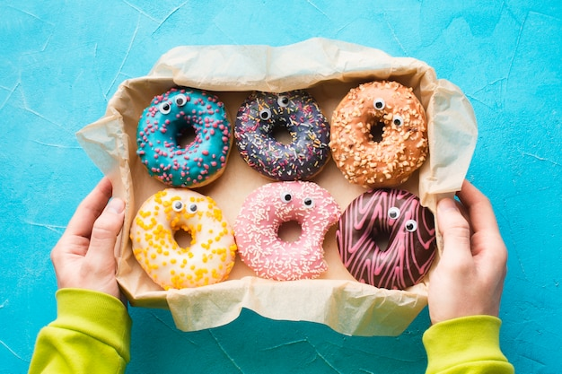 Mãos segurando uma caixa com donuts