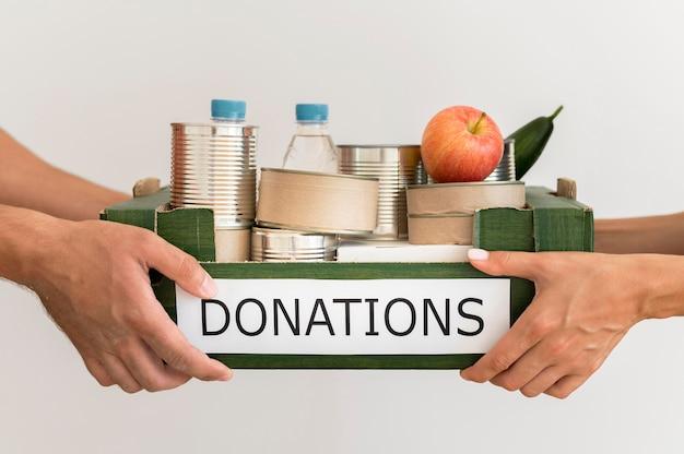 Mãos segurando uma caixa de doação com comida
