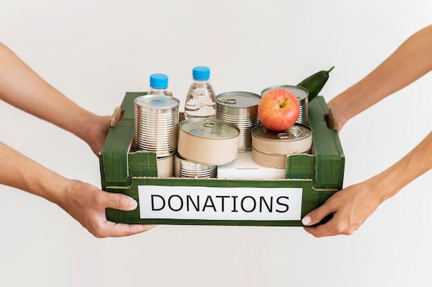 Mãos segurando uma caixa de doações com provisões