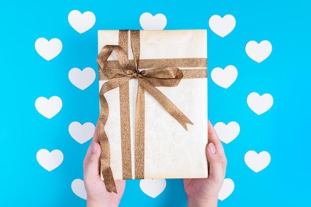 Mãos segurando uma caixa de presente amarela amarrada com uma fita marrom glitter sobre corações brancas colocadas em azul
