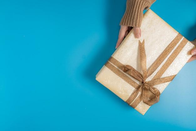 Mãos segurando uma caixa de presente amarrada com fita marrom azul
