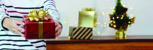 Mãos segurando uma caixa de presente de natal na celebração de natal