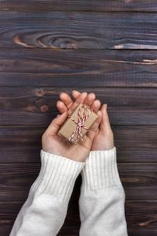 Mãos segurando uma caixa de presente de papel ofício com um presente para o natal