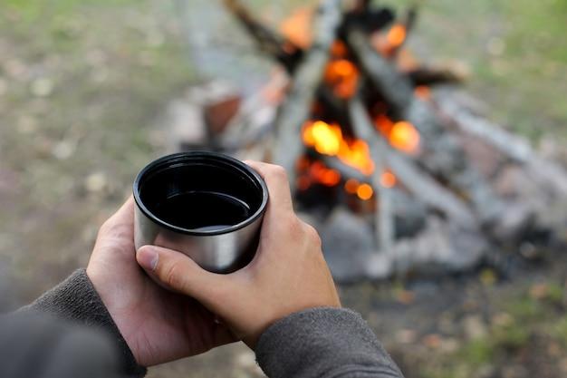 Mãos segurando uma caneca com chá na fogueira