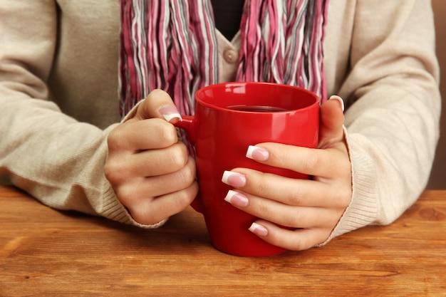 Mãos segurando uma caneca com close-up de bebida quente
