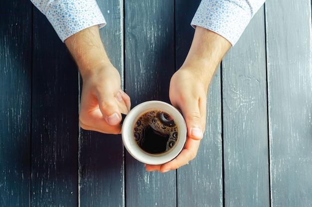 Mãos segurando uma caneca de bebida quente na mesa de superfície de madeira