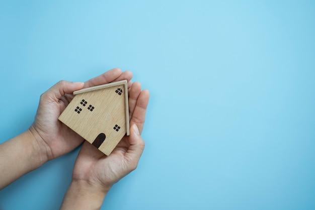 Mãos segurando uma casa de madeira velha em fundo azul pastel protegendo o conceito de seguro de casa