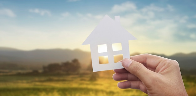Mãos segurando uma casa de papel, uma casa de família e protegendo o conceito de seguro