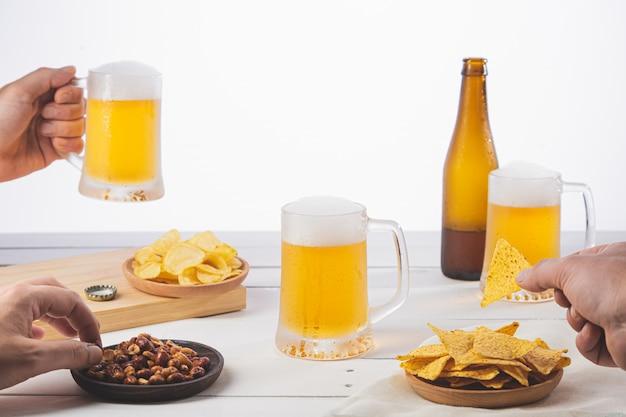 Mãos segurando uma cerveja e compartilhar um lanche na base de madeira branca