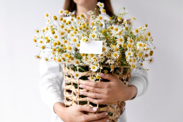 Mãos segurando uma cesta com flores de perto