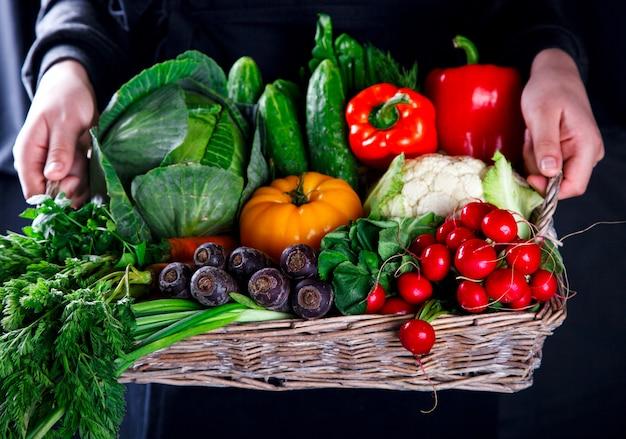 Mãos segurando uma cesta grande com diferentes legumes frescos da fazenda.