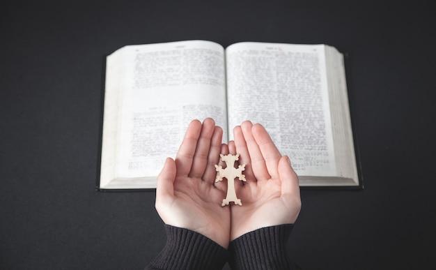 Mãos segurando uma cruz. conceito de religião