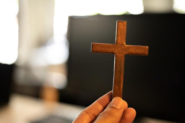 Mãos segurando uma cruz de madeira, conceito on-line da igreja. adoração em casa conceito.