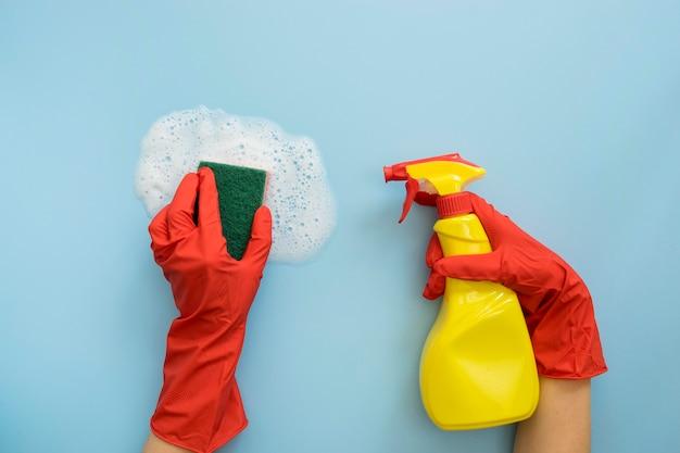 Mãos segurando uma esponja e frasco de spray