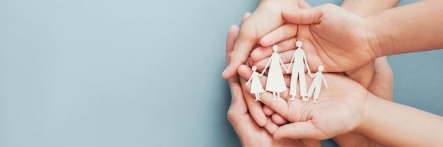 Mãos segurando uma família de papel