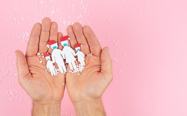 Mãos segurando uma família recortada em papel com máscara e chapéu de natal em um fundo rosa.
