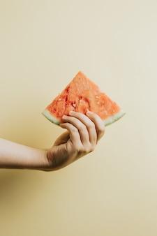 Mãos segurando uma fatia de melancia vista superior simulada com o conceito de verão do espaço de cópia