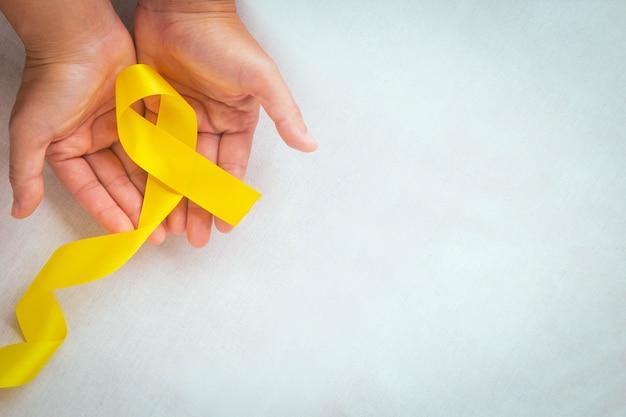 Mãos segurando uma fita amarela com espaço de cópia câncer ósseo conscientização do sarcoma conscientização do câncer infantil cholangiocarcinoma mundo do câncer de vesícula biliar dia da prevenção do suicídio conceito de seguro de saúde