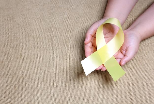 Mãos segurando uma fita amarela com espaço de cópia.