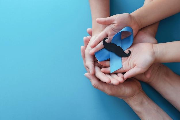 Mãos segurando uma fita azul com bigode, conscientização do câncer de próstata