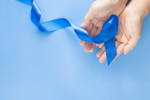 Mãos segurando uma fita azul profunda em fundo azul com espaço de cópia