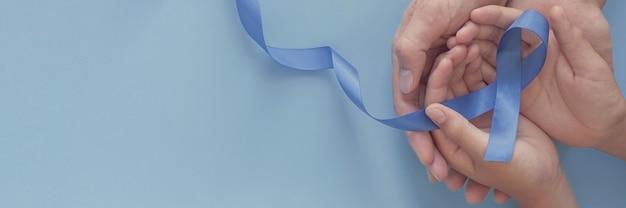Mãos segurando uma fita azul