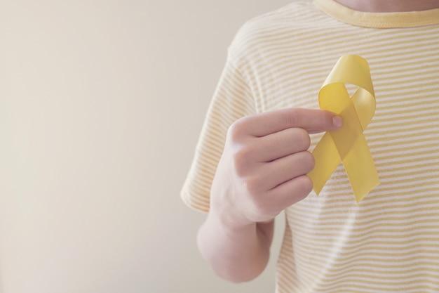 Mãos segurando uma fita de ouro amarelo, conscientização sobre o sarcoma, conscientização sobre o câncer infantil, conceito do dia mundial da prevenção do suicídio