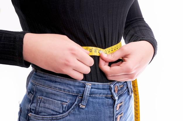 Mãos segurando uma fita métrica em volta do conceito de cintura, saúde e dieta.