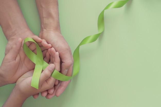 Mãos segurando uma fita verde, dia mundial da saúde mental