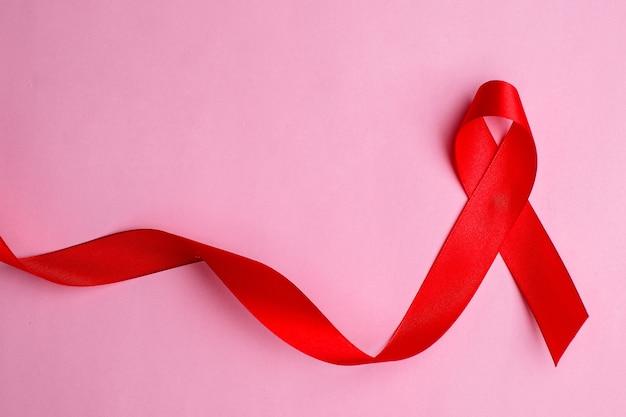 Mãos segurando uma fita vermelha, conceito de conscientização hiv, dia mundial da aids, dia mundial da hipertensão