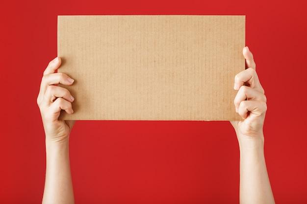 Mãos segurando uma folha de papelão em branco sobre uma superfície vermelha