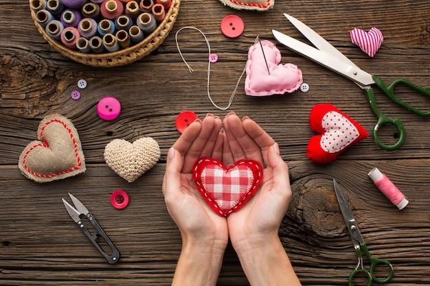 Mãos segurando uma forma de coração vermelho sobre fundo de madeira