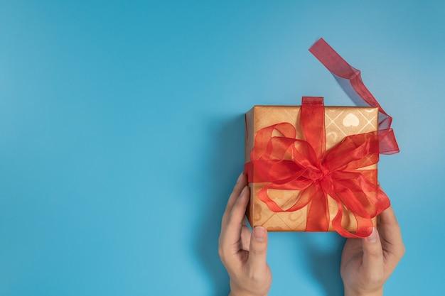 Mãos segurando uma grande caixa de presente amarrada com fita vermelha sobre azul
