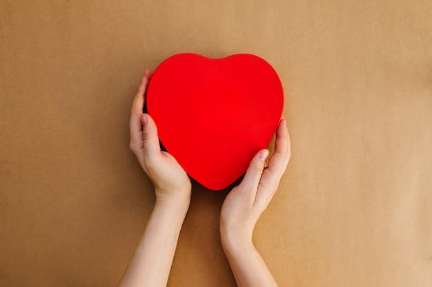 Mãos segurando uma grande caixa em forma de coração vermelho com fundo de papel kraft.