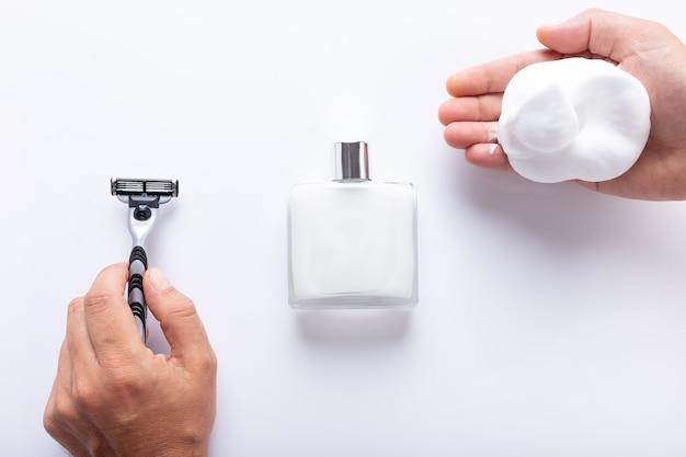 Mãos segurando uma lâmina de barbear e espuma de barbear, com pós-barba isolado na vista superior de fundo branco. produtos de barbear para homem.