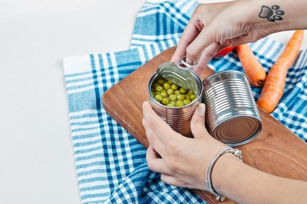 Mãos segurando uma lata de ervilhas cozidas em uma mesa branca com legumes e toalha de mesa.