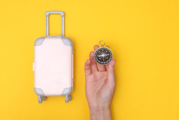 Mãos segurando uma mala de viagem de mini fantoche e uma bússola em fundo amarelo. tempo de viagem