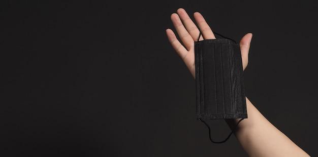 Mãos segurando uma máscara cirúrgica preta. máscara médica em fundo preto.