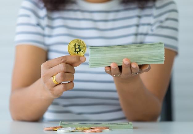 Mãos segurando uma moeda criptográfica e a pilha de dinheiro das notas e o gesto de comparação. conceito de investimento em ativos digitais e tesouro da velha escola.