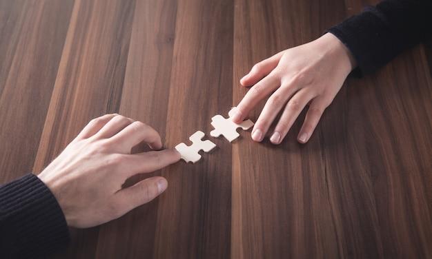 Mãos segurando uma peça de quebra-cabeça. solução, sucesso, trabalho em equipe